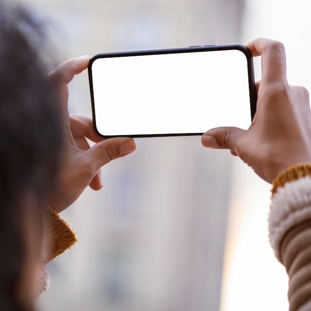 Vrouw die een leeg scherm-smartphone bekijkt Premium Foto