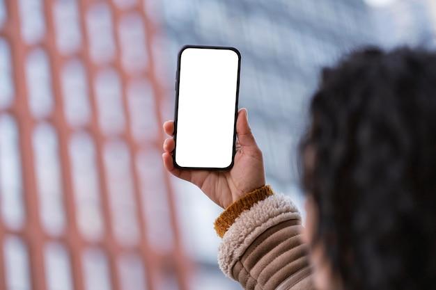 Vrouw die een lege smartphone bekijkt Premium Foto