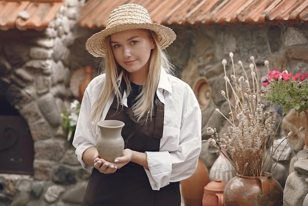 Vrouw die een met de hand gemaakte vaas houdt Gratis Foto