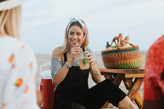 Vrouw die een mojito drinkt op een strandfeest Premium Foto
