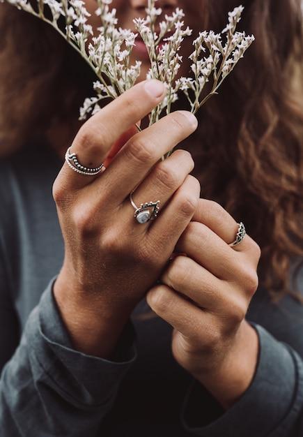 Vrouw die een mooie witte bloem houdt Gratis Foto