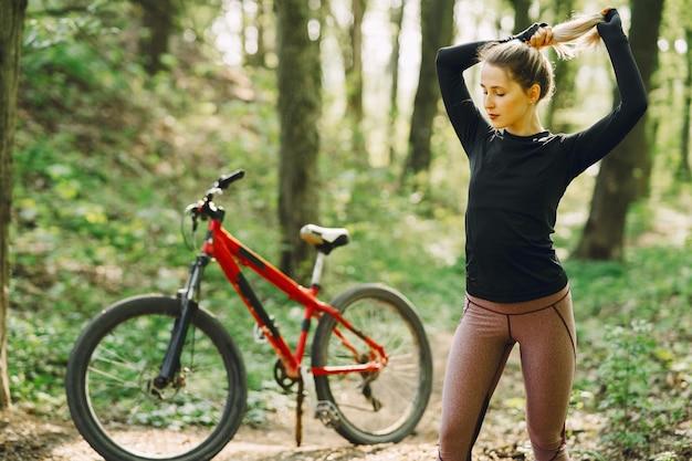 Vrouw die een mountainbike in het bos berijdt Gratis Foto