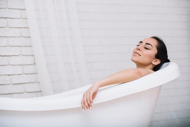 Vrouw die een ontspannend bad in een kuuroord neemt Gratis Foto