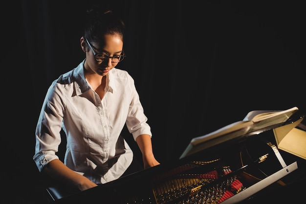 Vrouw die een piano in muziekstudio speelt Gratis Foto