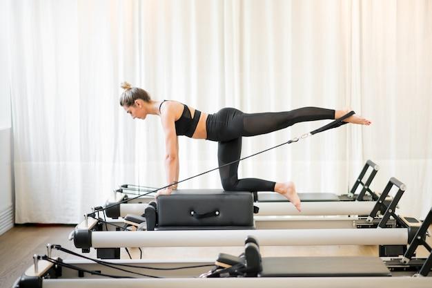 Vrouw die een pilates diagonale stabilisatie uitvoert Premium Foto