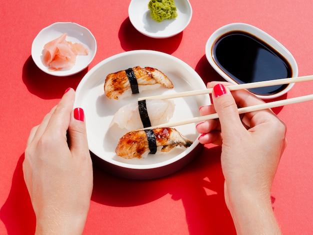 Vrouw die een plaat met sushi houdt Gratis Foto