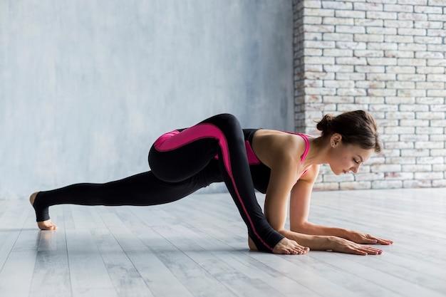 Vrouw die een plank met been uitvoert dat vooraan wordt uitgebreid Gratis Foto