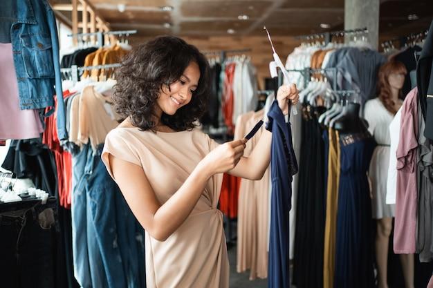 Vrouw die een prijskaartje bekijkt terwijl het winkelen kleding Premium Foto