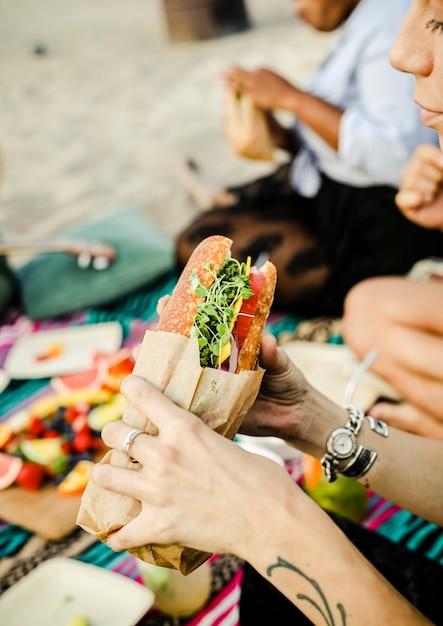 Vrouw die een sandwich eet bij het strand Gratis Foto