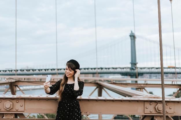 Vrouw die een selfie op de brooklyn bridge, verenigde staten Premium Foto