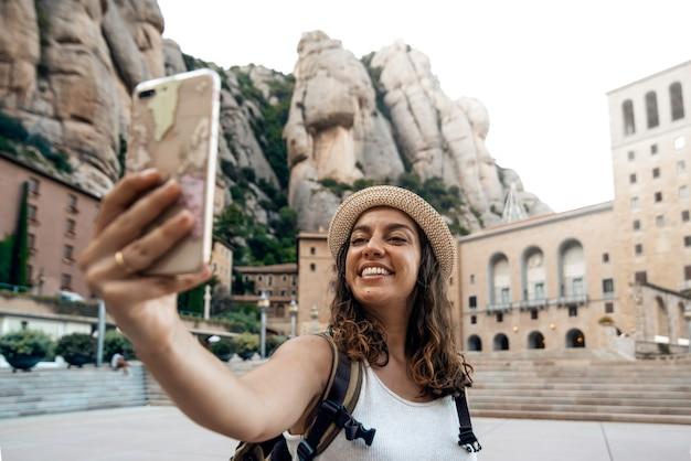 Vrouw die een selfiefoto neemt in het klooster van montserrat, barcelona, spanje Premium Foto