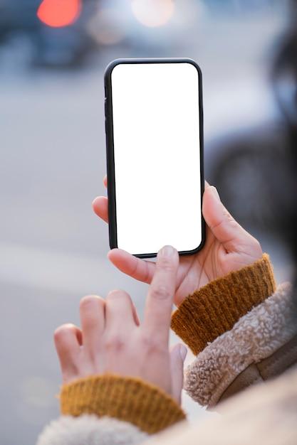 Vrouw die een smartphone met een leeg scherm controleert Gratis Foto