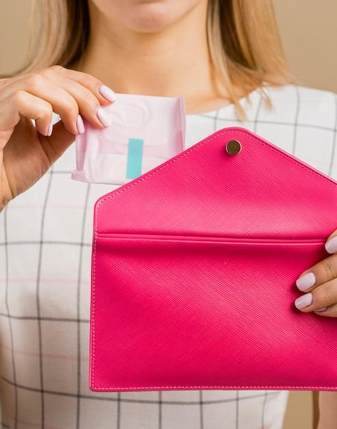 Vrouw die een stootkussen van haar portefeuille toont Gratis Foto