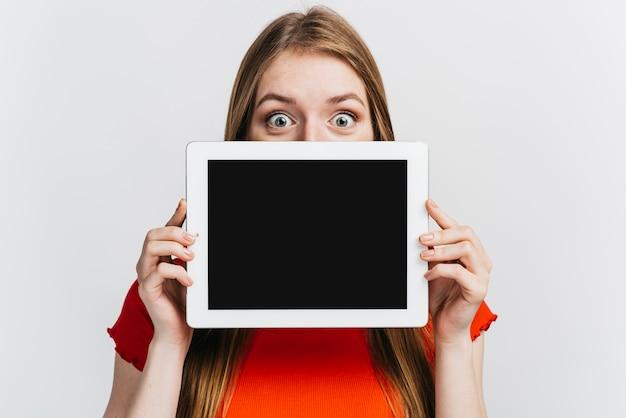 Vrouw die een tablet voor haar gezichtsmodel houdt Gratis Foto