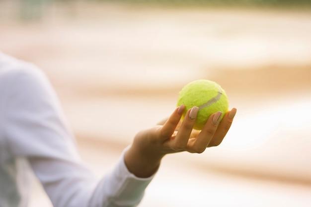 Vrouw die een tennisbal in een hand houdt Gratis Foto