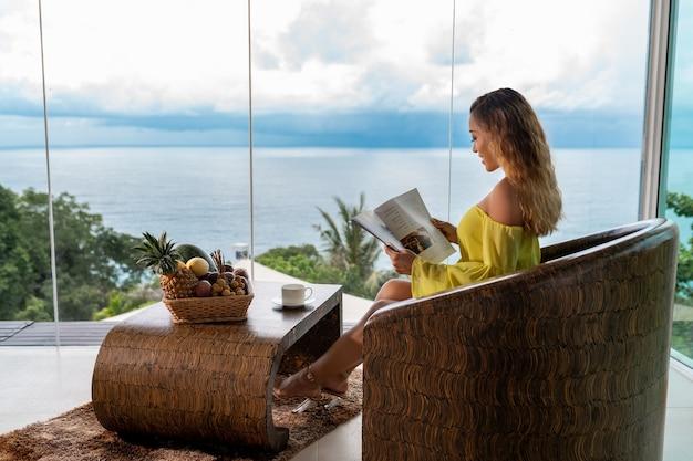 Vrouw die een tijdschrift op een balkon leest Premium Foto