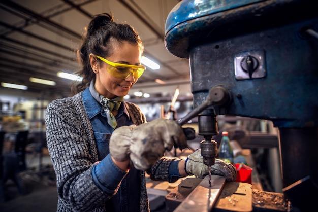 Vrouw die een verticale machine met behulp van om een gat in metaal te maken terwijl status in workshop Premium Foto