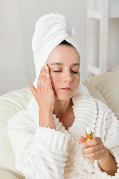 Vrouw die een vochtinbrengende crème voor haar huid gebruikt en een badjas draagt Premium Foto