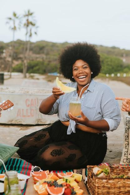 Vrouw die een watermeloen eet bij een strandpicknick Premium Foto