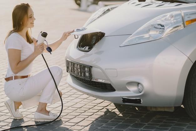 Vrouw die elektro auto laadt bij het elektrische benzinestation Gratis Foto