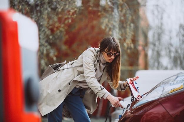 Vrouw die elektrocar laadt bij het elektrische benzinestation Gratis Foto