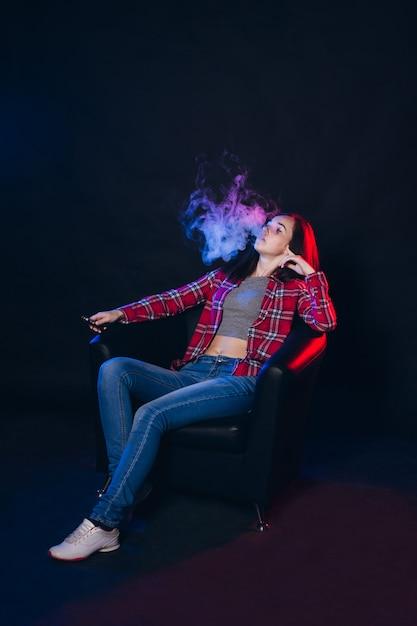 Vrouw die elektronische sigaret met rook rookt Premium Foto