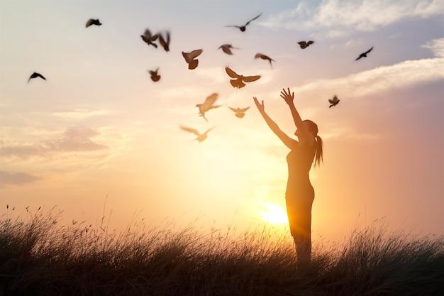 Vrouw die en de vogels bidden bevrijden aan aard op zonsondergangachtergrond Premium Foto