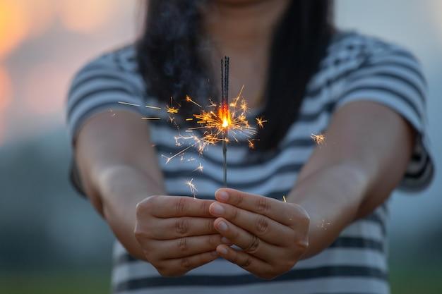 Vrouw die en met vuursterretjes op het festival in het padieveld houden houden in zonsondergangtijd Premium Foto