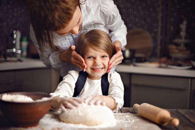 Vrouw die en pret met meisje kookt heeft Premium Foto