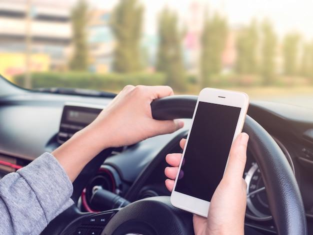 Vrouw die en smartphone op weg drijft gebruikt Premium Foto