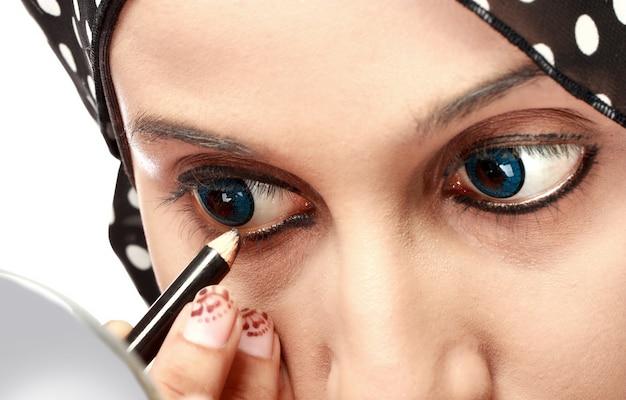 Vrouw die eyeliner toepast Premium Foto