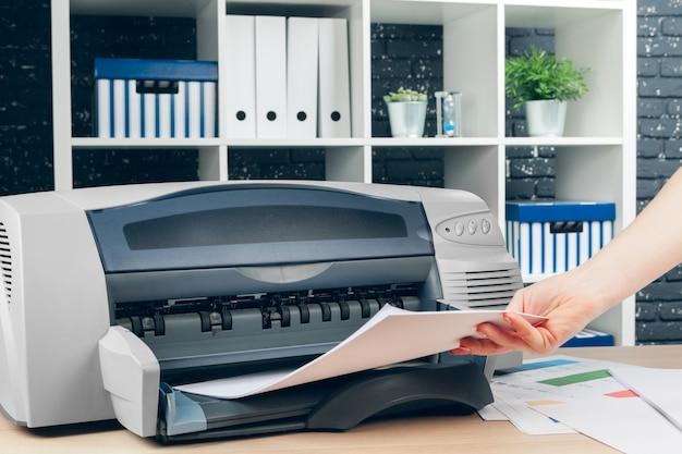 Vrouw die fotokopie maakt die kopieerapparaat in bureau met behulp van Premium Foto