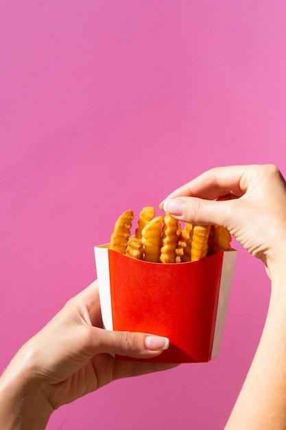 Vrouw die frieten van rode doos eet Gratis Foto