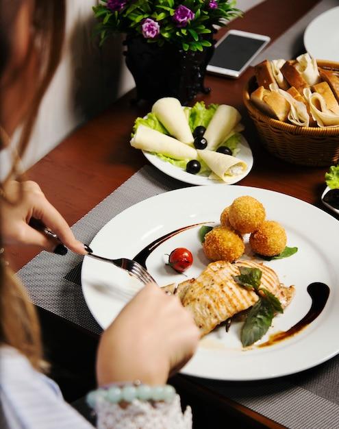 Vrouw die gebakken zalmfilet met aardappels en kaasbroodjes, en groentenmengeling eet. Gratis Foto