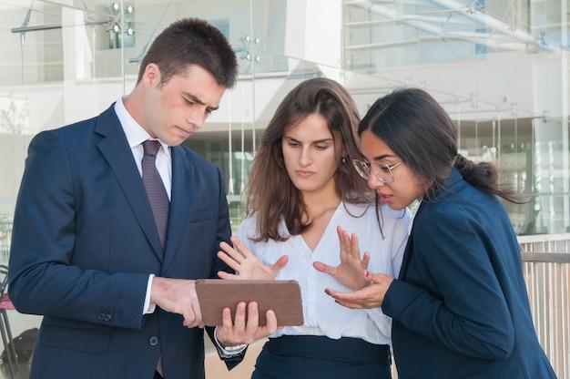Vrouw die gegevens over tablet toont, iedereen die sceptisch kijkt Gratis Foto