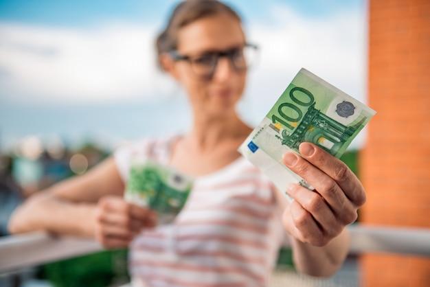 Vrouw die geld geeft Premium Foto
