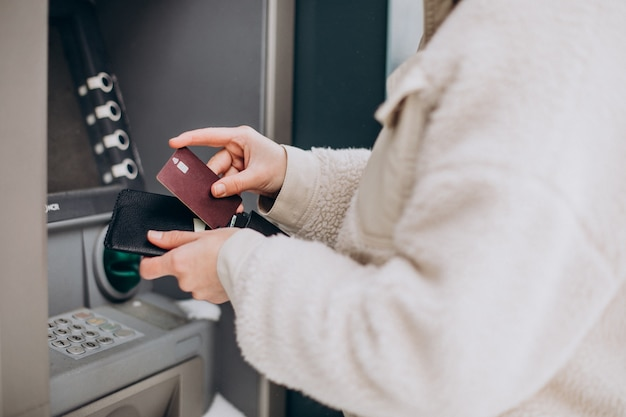 Vrouw die geld opneemt bij pinautomaat buiten de straat Gratis Foto