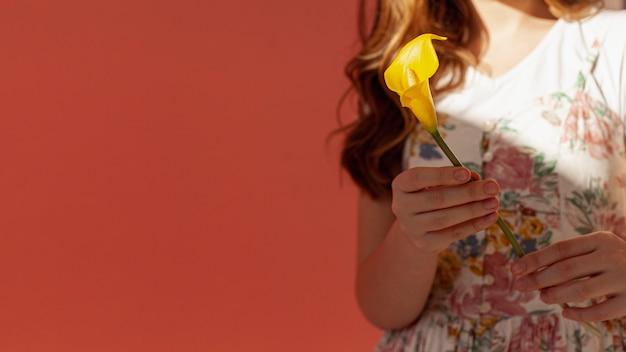 Vrouw die gele calla lelie houdt Gratis Foto