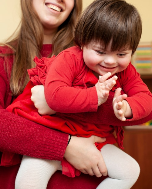 Vrouw die gelukkig kind met downsyndroom houdt Gratis Foto