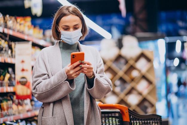 Vrouw die gezichtsmasker draagt en in kruidenierswinkelopslag winkelt Gratis Foto