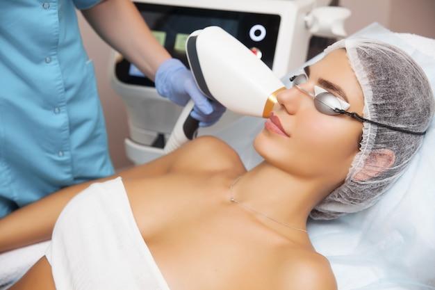 Vrouw die gezichtsschoonheidsbehandeling ontvangt, die pigmentatie verwijdert bij kosmetische kliniek. Premium Foto