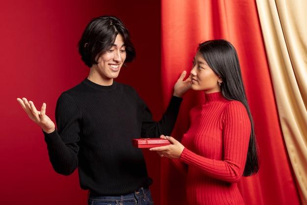 Vrouw die gift aanbiedt aan de mens voor chinees nieuw jaar Gratis Foto