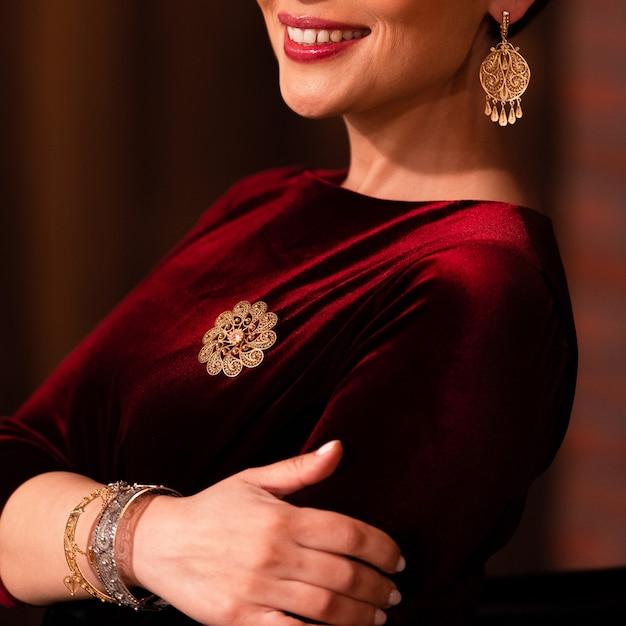 Vrouw die gouden oosterse stijljuwelen aantoont Gratis Foto
