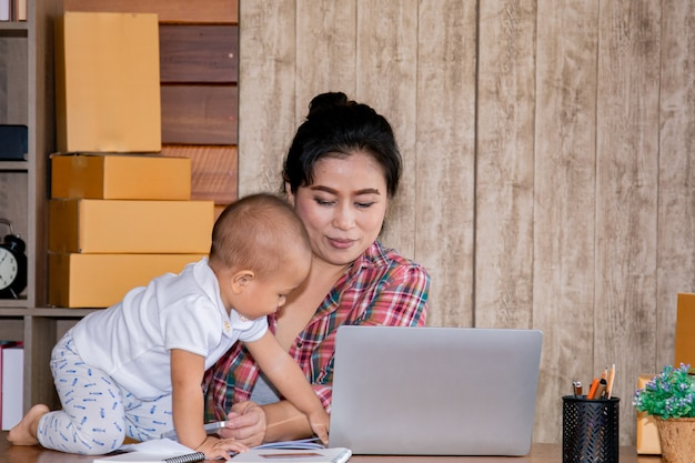 Vrouw die haar baby behandelt terwijl het werken op het kantoor Premium Foto