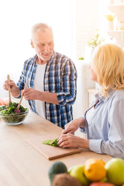 Vrouw die haar echtgenoot bekijkt die de salade in de keuken voorbereidt Gratis Foto