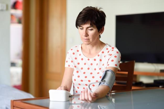 Vrouw die haar eigen bloeddruk thuis meet. Premium Foto