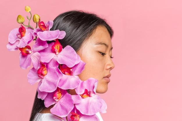 Vrouw die haar gezicht zijdelings behandelt met orchideebloemblaadjes Gratis Foto
