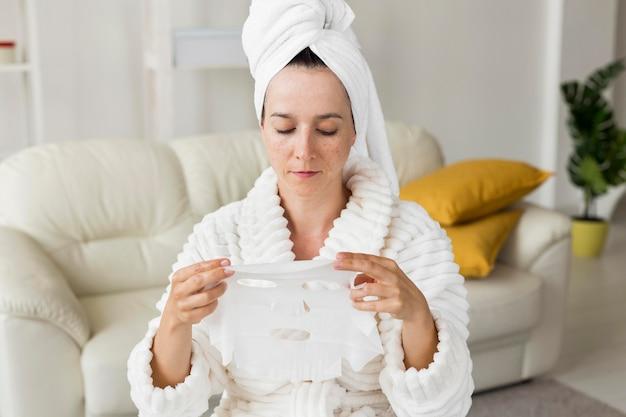 Vrouw die haar gezichtsmasker kijkt Gratis Foto