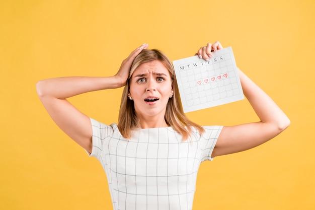 Vrouw die haar handen op haar hoofd en periodekalender zet Gratis Foto
