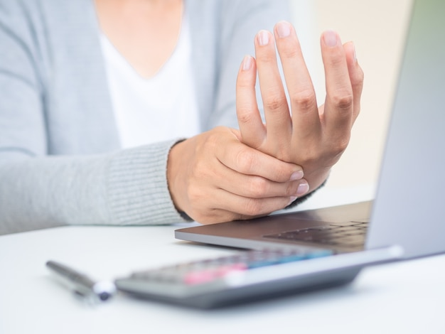 Vrouw die haar handpijn van het gebruiken van oude computer houdt Premium Foto